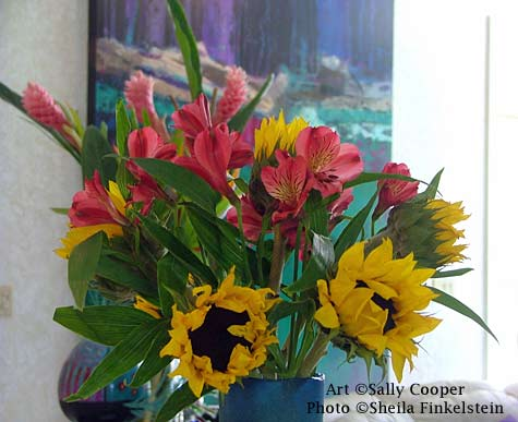 sunflowers and alstroemeria in front of a painting.